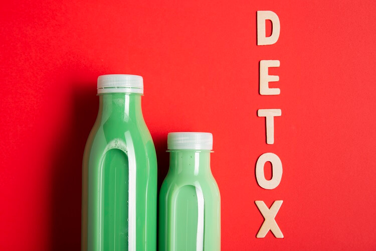 two bottles with green juice and the word detox in vertical format