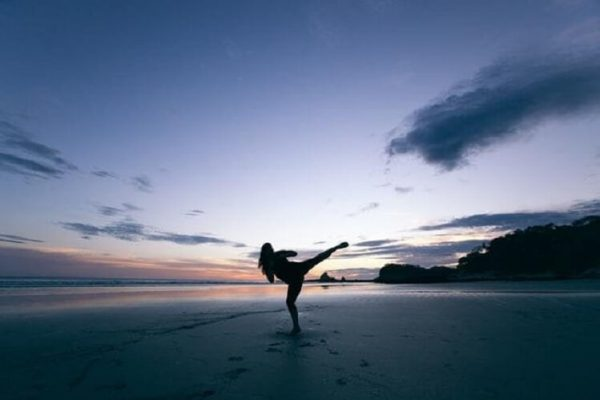 person doing karate on a beach