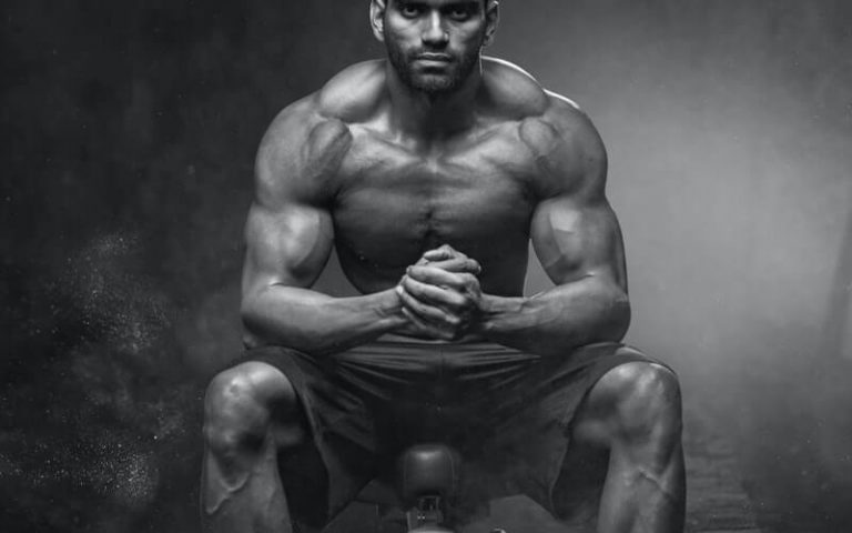 muscled man sitting on a bench