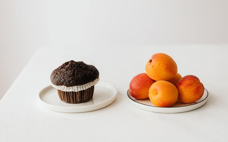 A Chocolate Muffin next to a group of apricots